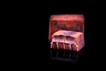 Japanese soft chocolate named Nama (also called raw chocolate) covered with cacao powder in black background