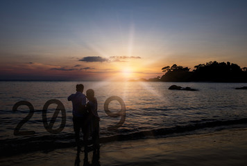 Concept new year 2019. Silhouette Couple standing on the beach watching the sunset to new yeat 2019.