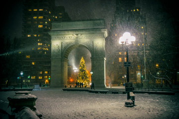 Winter holiday night view of the Washington Square Park with a Christmas Tree under falling snow in New York City