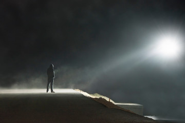 A lone hooded figure standing on a spooky misty road at night looking at a UFO light in the nights sky