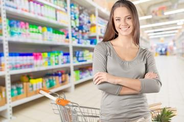 Young happy woman pushing shopping cart