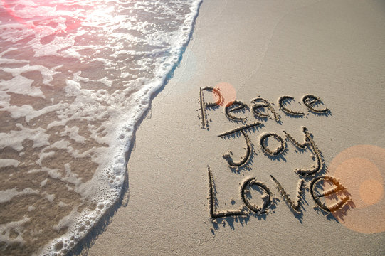 Happy holiday message of Peace, Joy, and Love handwritten in smooth sand with an oncoming wave in the lens flare of the tropical sun