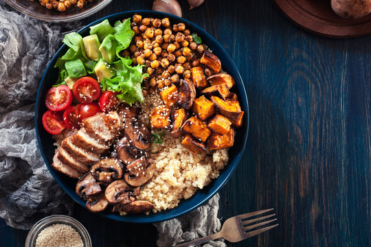 Vegetable buddha bowl lunch with chicken and quinoa, chickpea, mushrooms, lettuce and tomatoes