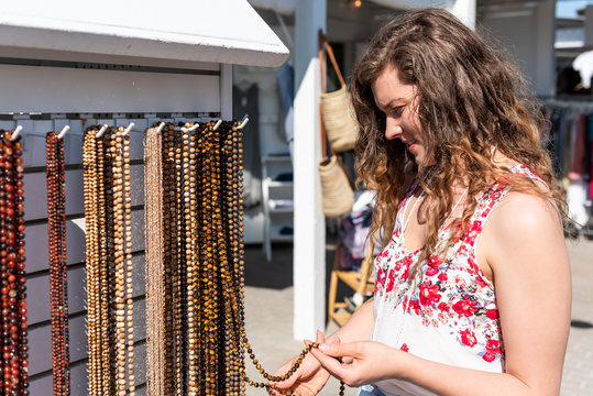 Young woman shopping for colorful stone beach necklaces jewelry touching hand in outdoor market shop store in European, Greece, Italy, Mediterranean town, destination in summer