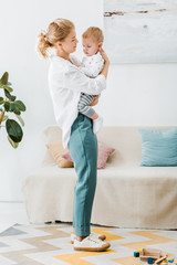 attractive mother standing and embracing adorable toddler son in living room