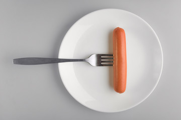 Concept diet, healthy food. One sausage on a white plate, sausage on a fork on a gray background.