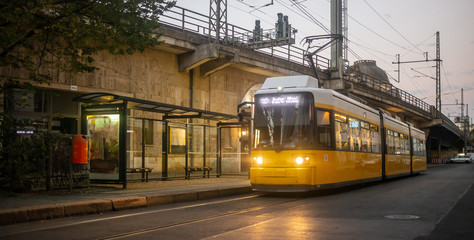 Public transportation concept. Yellow electric tram at Berlin, Germany. Cloudy sky background.