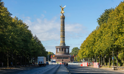 Berlin Victory Column. Golden statue of angel tries to touch the sky. Clouds, trees background.