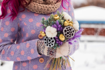 A woman with pink hair in a coat and mittens is from the original bouquet of dried flowers