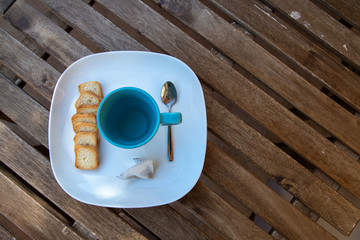 Blue cup of hot wather with fiter tea top view on wooden table background brown saucer and teaspoon small slices of toast breakfast on the terrace snack nice break from work