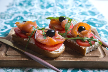 Healthy snack or salmon fish, arugula, olives and creamy cheese on toast bread. French or italian organic breakfast