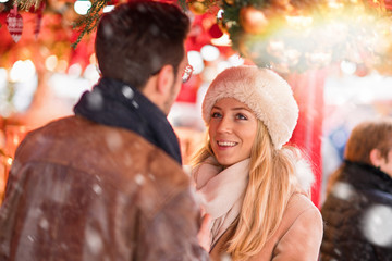 Christmastime. A couple walks in the decorated streets