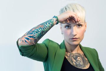 Ragazza bionda con tatuaggi nel petto e nelle braccia, vestita con una giacca verde si tiene la testa e guarda in macchina Fotomurales