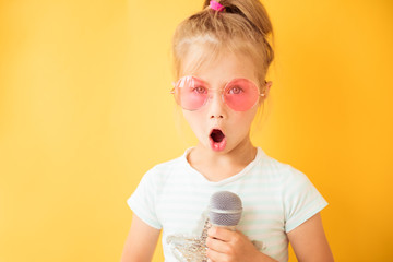 Happy little girl singing into a microphone the song on yellow background