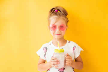 Acrylic Prints Milkshake Little girl standing with milkshake in hand on yellow background