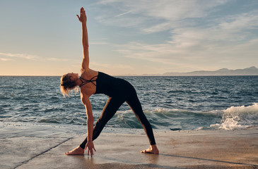 Young woman standing in Triangle Pose near sea