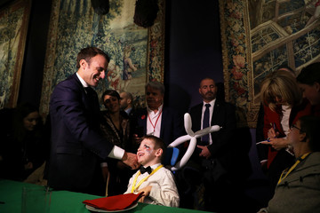 French President Emmanuel Macron speaks with a guest during the Christmas Party for the children of Elysee Palace's employees at the Gobelins Manufactory, in Paris