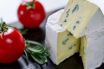 Assorted cheeses on wooden board. Camembert, cheese with blue mildew, mozzarella with tomatoes