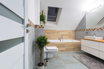 Modern bathroom interior with gray tiles and wooden decors