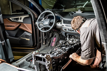 A mechanic repairs a luxury SUV Repair wiring, gearboxes, disassembled interior premium crossover. Removed chairs. Leather interior. Neat repair service center.