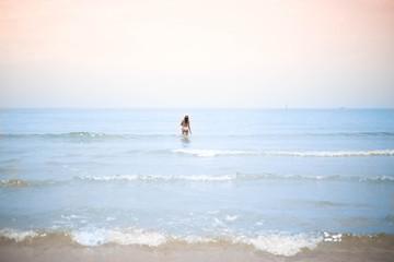 mujer bañándose en el mar con sombrero de paja