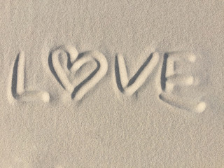 Beach background with love written in the sand.