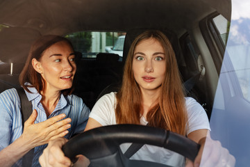 Surprised girl with her mother driving a car Fototapete