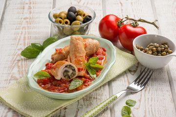 stuffed roll of turkey with capers olives and tomatoes sauce