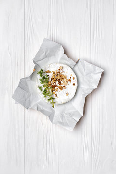 Gourmet appetizer of white brie cheese or camembert with thyme and nuts