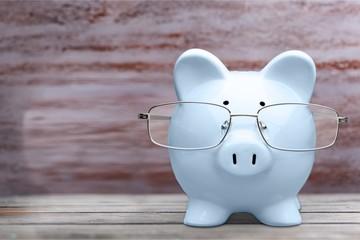 Piggy bank in glasses on desk