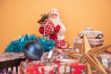 Дед Мороз с подарками и елочными игрушками на желтом фоне