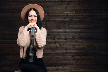 Young beautiful woman sitting on a chair with ukulele wearing a hat. Girl with hands folded on a small guitar on a dark wooden background.