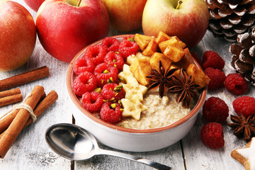 Bowl of oatmeal porridge with banana, apples,raspberries coconut and caramel sauce on rustic table, hot and healthy food for Breakfast