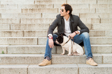 Man sitting on a stairs next to his dog.