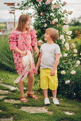 Summer portrait of two stylish kids posing in flower garden on a nice sunny day