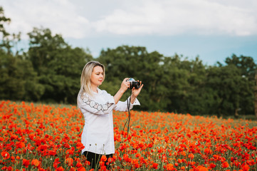 Beautiful woman photographer enjoying amazing day at poppy field, holding vintage film camera