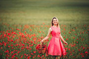 Beautiful woman with blond hair enjoying amazing view of poppy field, wearing pink dress. Image taken in Geneva, Switzerland