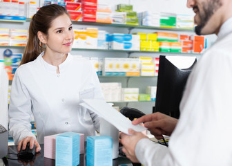 Woman pharmacist is recommending medicine for man client in apot