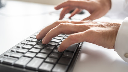 Low angle closeup view of male hands typing