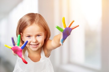 Cute little girl with colorful painted hands on white background
