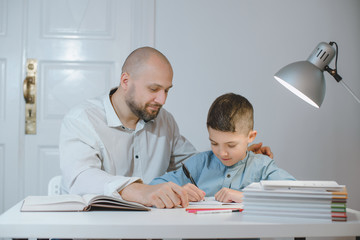 Father and son work together on school homework or homeschooling.