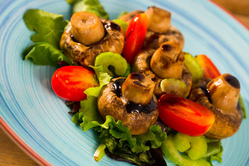 Baked champignons with spinach, lettuce, tomatoes, celery