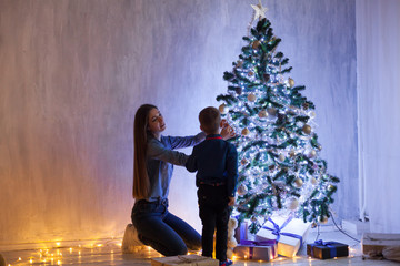 mom with son decorate decoration Christmas tree have new year holiday house