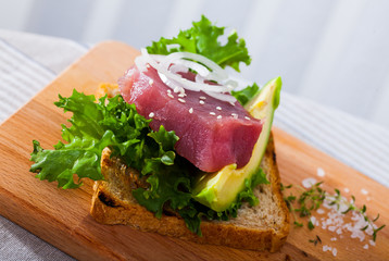 Tasty sandwich with raw tuna, avocado and greens  at plate