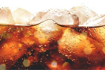 Fototapeta Ice cubes in cola beverage, close up