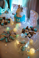 Delicious wedding reception candy bar dessert table full with cakes, sweets, macaroons, eclairs and other types of bakery
