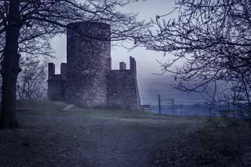 Old ruins of a defense tower covered in fog creating a mystical scene.