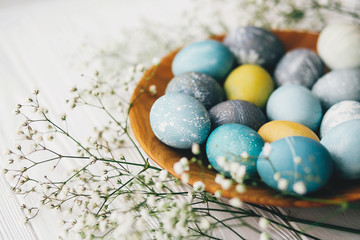 Stylish easter eggs with spring flowers on wooden plate on white wooden background. Modern easter eggs painted with natural dye in blue, grey, yellow marble color. Happy Easter