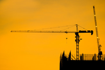 Crane and building construction site at sunset. High-quality stock photo image silhouette of construction tower crane group with sunset sky background. Building construction with crane during sunset