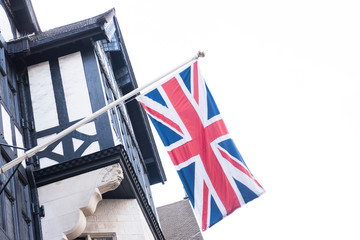 Closeup of a Birtish Flag or Union Jack is seen hanging from a building. The glass windows along with the clear bright sky is also seen in the picture.